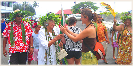Sokala Villas' guest Evelyne Haller from Switzerland is invited to touch the Queen's Baton as it is carried in Avarua by a High Chief of Te Au-O-Tonga, Margaret Karika Ariki