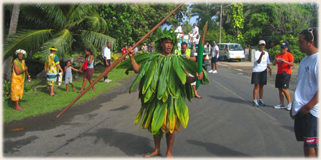 A convergence of the old and new. A Rarotongan traditional leader holds a ceremonial spear in his right hand and the Queen's Baton in his left as he performs a welcome turou.