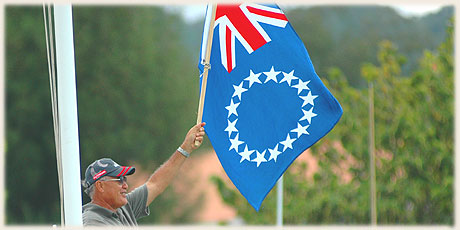 Ted Nia - holding up the national flag during Round Raro OC1 Relay Race / Photo by Lawrance Bailey © sokalavillas.com